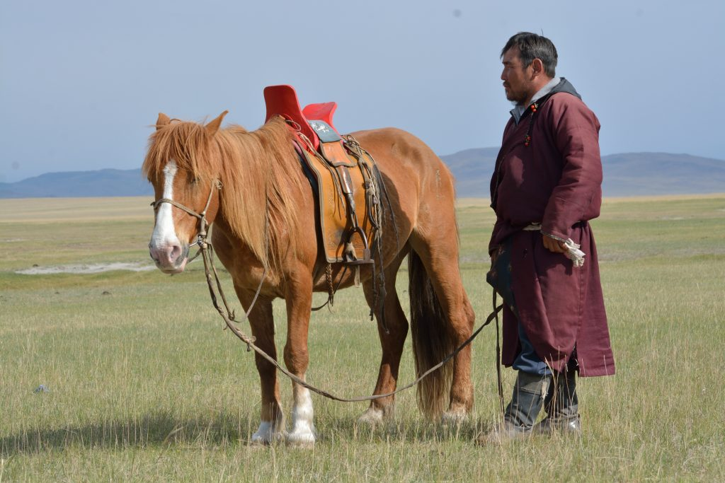 nomadic herder with his horse Mongolian steppe